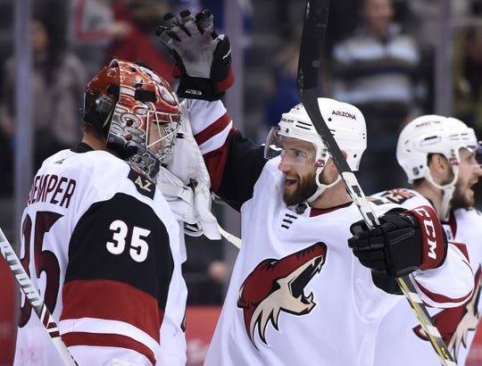 Coyotes goalie Darcy Kuemper is greeted by defenseman Alex Goligoski after Sunday's win over the Maple Leafs.