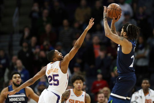 Minnesota Timberwolves' Derrick Rose shoots the game-winning shot over Phoenix Suns' Mikal Bridges in the first half of an NBA basketball game Sunday, Jan. 20, 2019, in Minneapolis. Minnesota won 116-114.