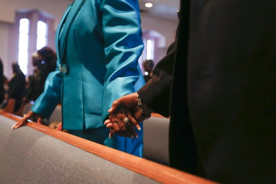 A couple holds hands in prayer at First Institutional Baptist Church on Sunday, Jan. 20, 2019.