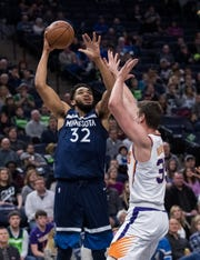 Jan 20, 2019; Minneapolis, MN, USA; Minnesota Timberwolves center Karl-Anthony Towns (32) shoots in the fourth quarter against Phoenix Suns forward Dragan Bender (35) at Target Center. Mandatory Credit: Brad Rempel-USA TODAY Sports