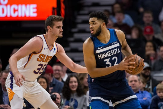 Jan 20, 2019; Minneapolis, MN, USA; Minnesota Timberwolves center Karl-Anthony Towns (32) dribbles in the second quarter against Phoenix Suns forward Dragan Bender (35) at Target Center. Mandatory Credit: Brad Rempel-USA TODAY Sports