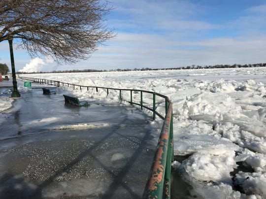 Benches in Marine City are covered in ice spilling over from the St. Clair River.