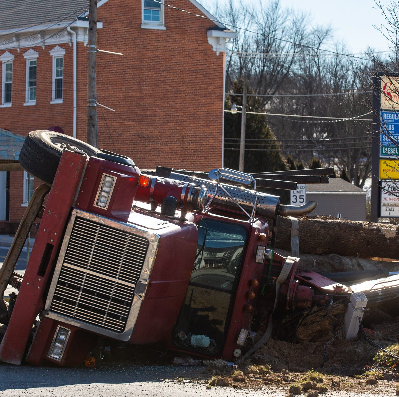 Logging truck rolls over at Jefferson square