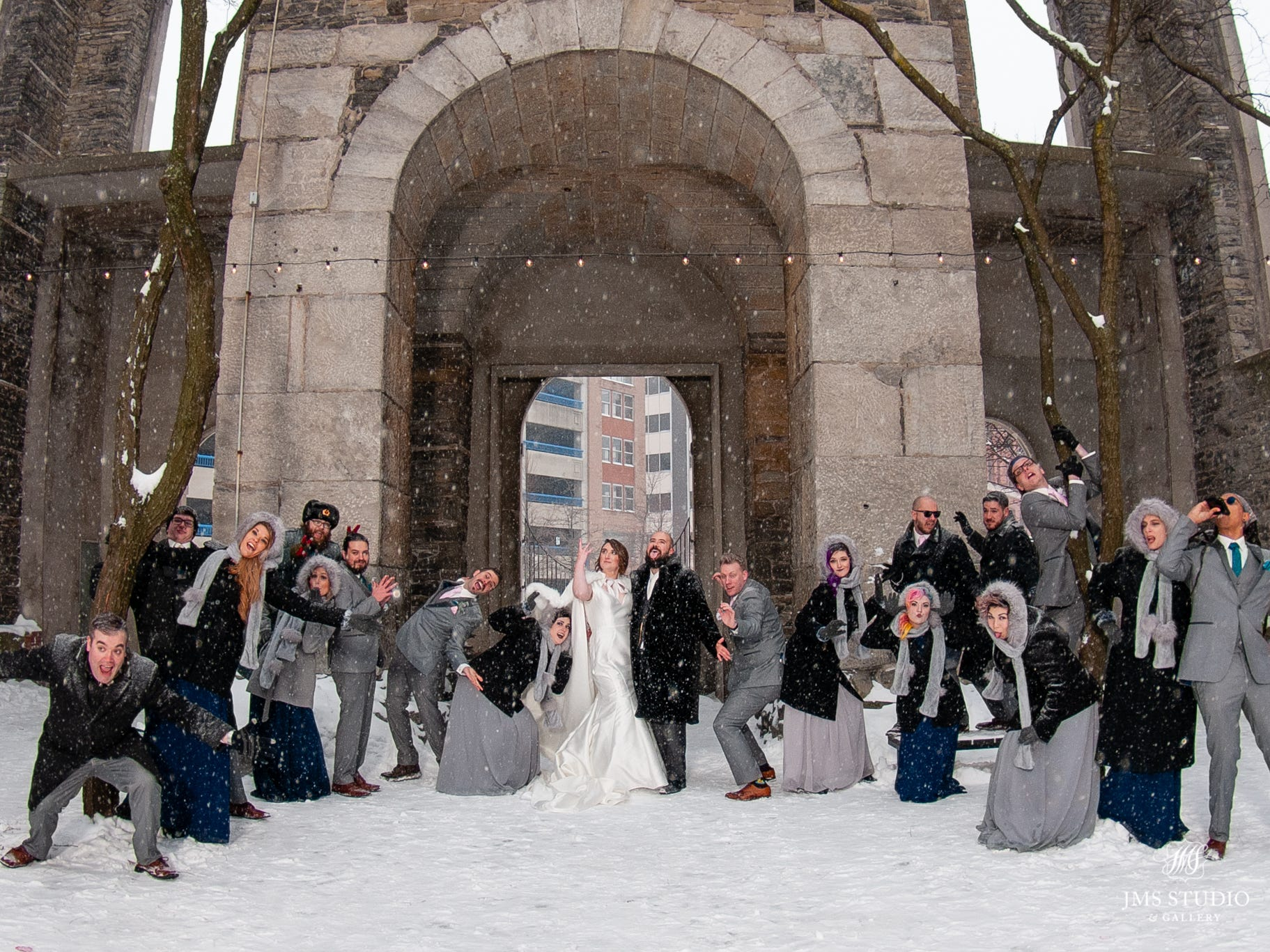 Darla and David Bragg, along with their wedding party, pose in the snow in St. Joseph's Park in downtown Rochester.