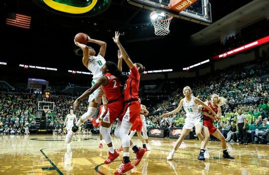 Oregon forward Satou Sabally (0), shoots over Arizona defenders during an NCAA college basketball game Sunday, Jan. 20, 2019, in Eugene, Ore.