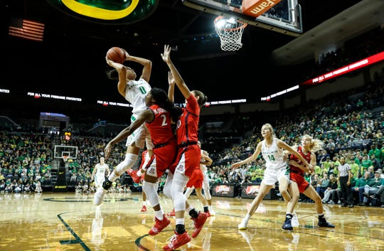 Oregon forward Satou Sabally (0), shoots over Arizona defenders during an NCAA college basketball game Sunday, Jan. 20, 2019, in Eugene, Ore.