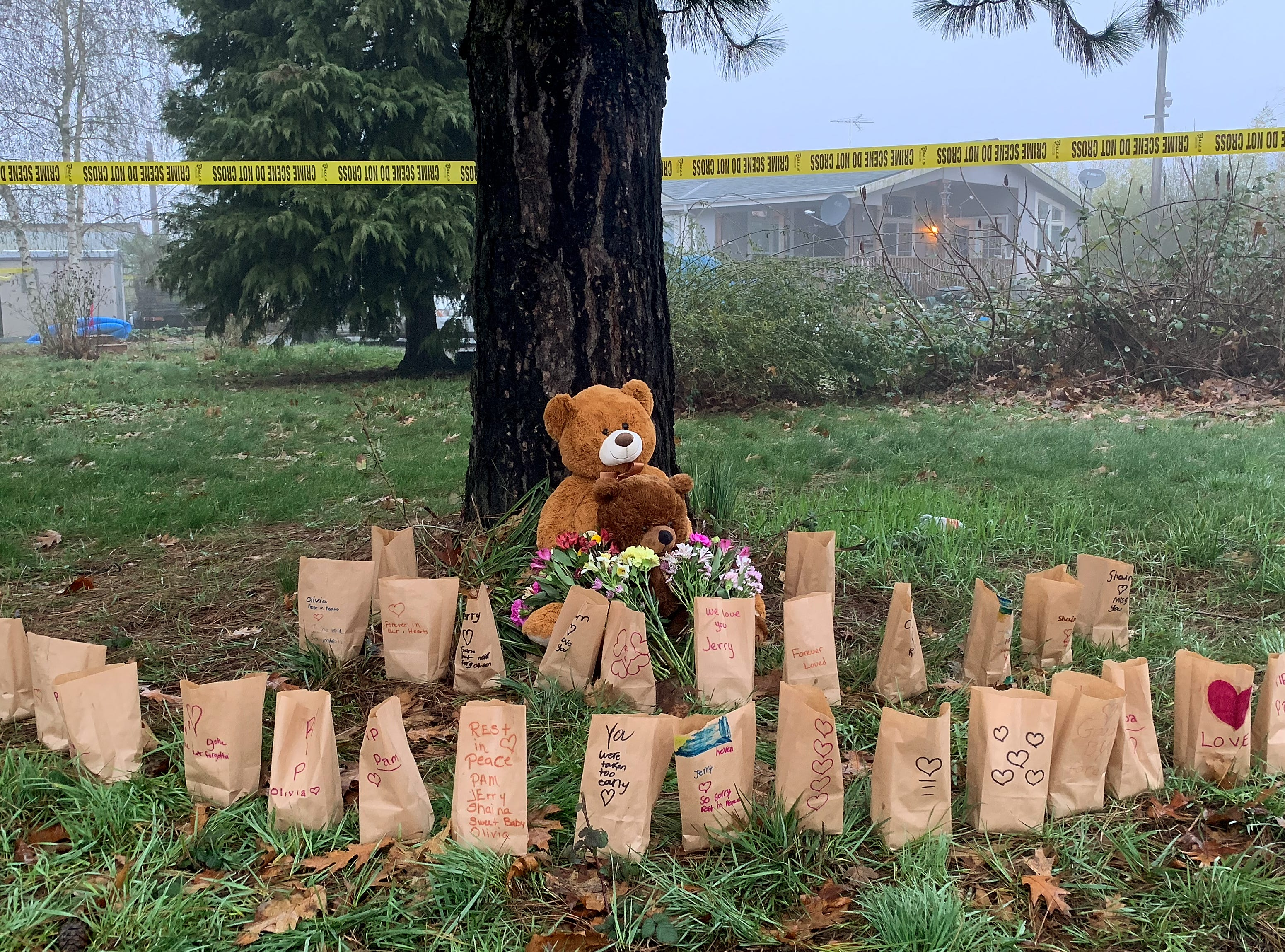 A memorial is growing for the victims of the quadruple homicide in the 32000 block of Barlow Rd. S near Woodburn, Oregon, over the weekend. Crime scene tape still outlines the property following the incident where the suspect, Mark Gago was shot and killed by deputies on Saturday night. A teddy bear, flowers and luminaries with messages to the victims surround a tree at the front of the property Monday morning, January 21, 2019.