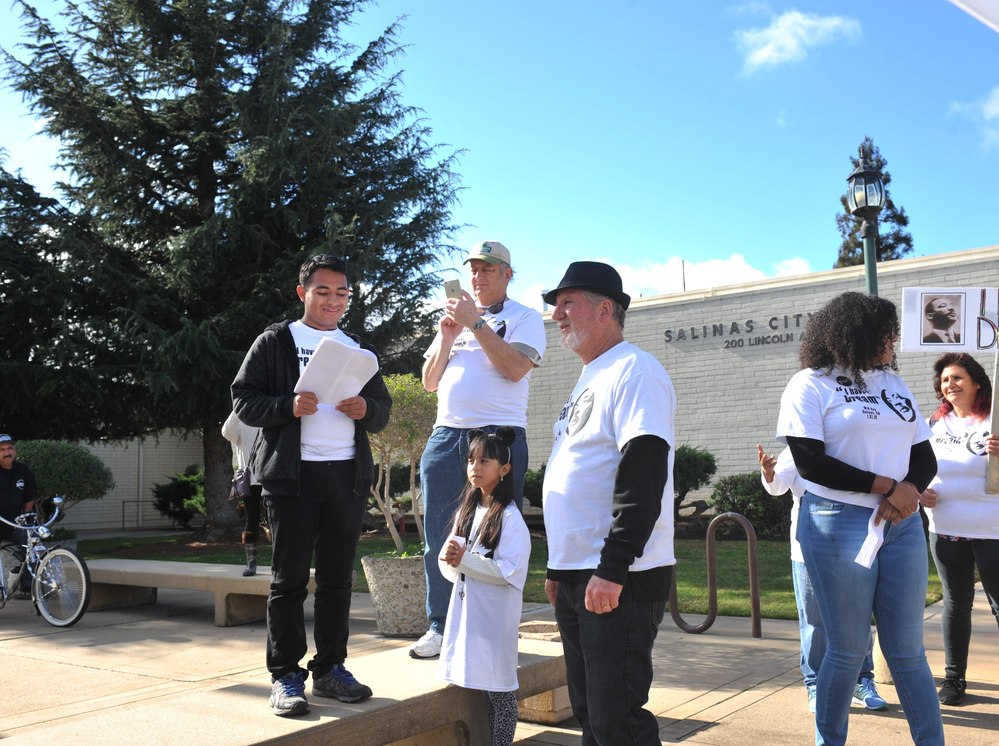 Alisal High School senior Daniel Regalado, far left, translates Martin Luther King Jr. quotes from English to Spanish in front of Salinas City Hall while his sister Gabriela, middle below, and the Rev. Steve Lundin, third from right, listen.