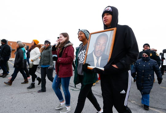 Payton and Essense Norris carry a portrait of Martin Luther King Jr. during the annual Martin Luther King Jr. March and Celebration in downtown Springfield on Monday, Jan. 21, 2019.