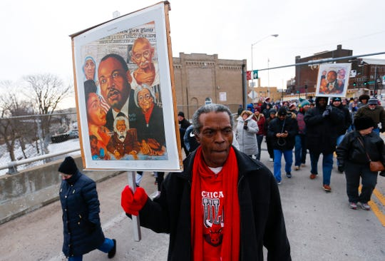 Calvin Allen carries a poster of civil rights activists during the annual Martin Luther King Jr. March and Celebration in downtown Springfield on Monday, Jan. 21, 2019.