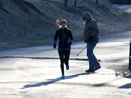 Jessi Locklear of Staunton runs past a Parks and Recreation employee who is bundled up against the cold morning temperature of 8 degrees. Locklear runs in the brisk cold around Gypsy Hill Park on Monday morning, Jan. 21, 2019. She runs in all types of weather, regardless of the conditions.