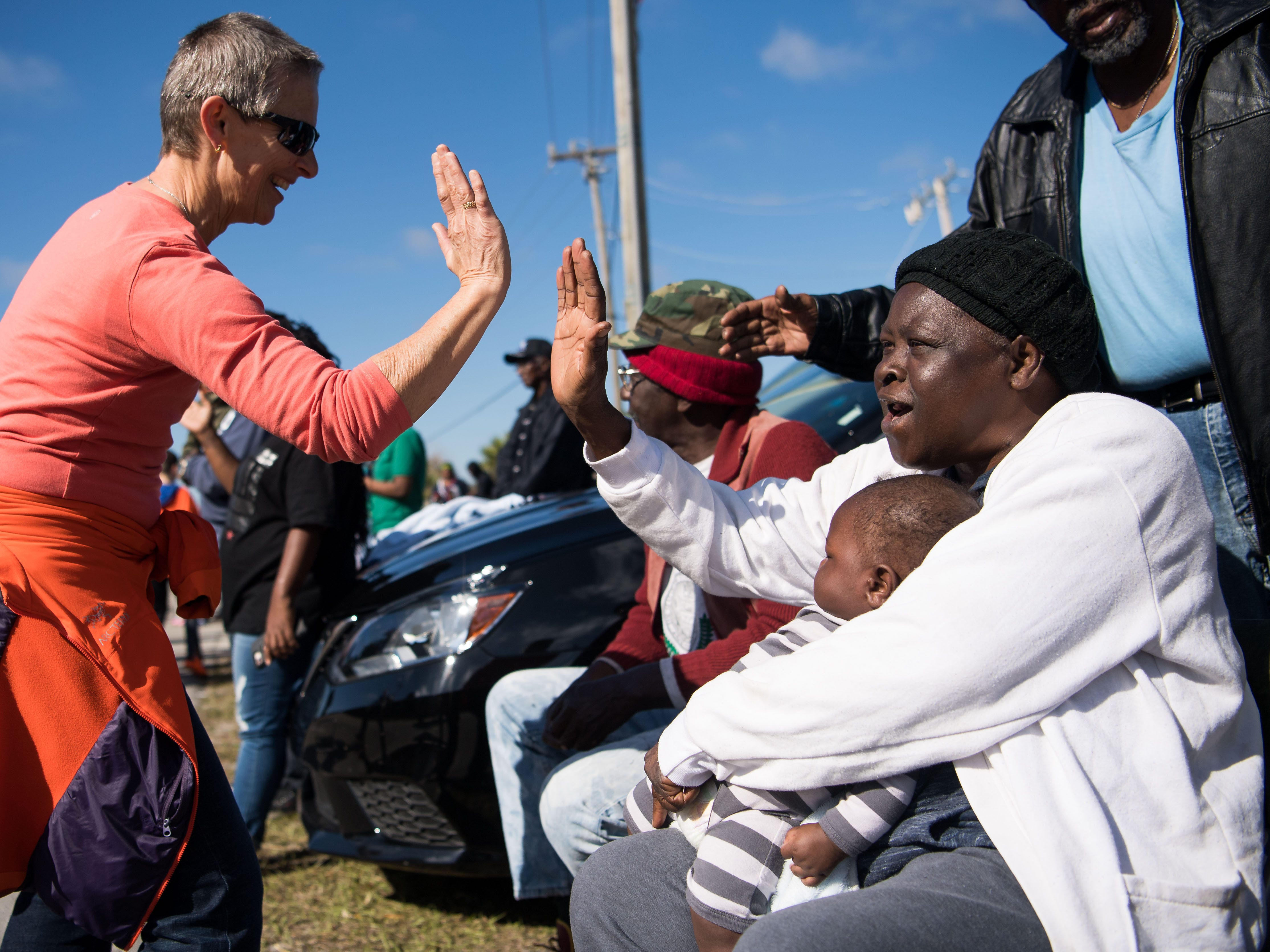 "Lifelong Gifford resident Corine Smith (right) — surrounded by her grandchildren, great-grandchildren and other family members — is high-fived by Unitarian Universalist Fellowship of Vero Beach member Dhumavati Jaya, of Sebastian, during the 2019 Martin Luther King Parade on Monday, Jan. 21, 2019, in Gifford. ""When they said he got shot, I was 10 years old at that time. ... I still listen to his speech, it means a lot,"" Smith said. ""God made us all, you know, he just made different colors,"" she added, ""but we are all his children."" The Dr. Martin Luther King Jr. Birthday Committee of Indian River County organized the parade, which ended in a festival at Gifford Park."