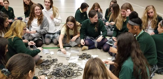 Members of Our Lady of Mercy Academy Interact Club package each Paracord Survival bracelet with a personal note of encouragement and thanks.