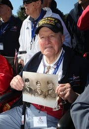 WWII veteran Adam Krainak of Spring Valley holds a photo of himself (center) on Oct. 18, 2014, at the National World War II Memorial in Washington, D.C. A group of local veterans were there as part of the Hudson Valley Honor Flight program.