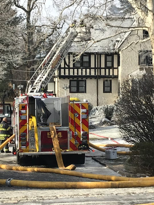 Firefighters take frost off the roof of the house at 72 Mamaroneck Road in the waning stages of battling a three-alarm fire that burned through the house Jan. 21.