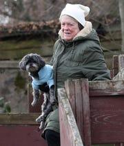Kris Philipps carries her dog Elizabeth on a walk in Piermont Jan. 21, 2019.