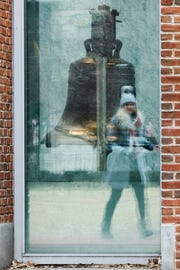 FILE - In this Wednesday, Jan. 16, 2019 file photo a tourist is reflected in a window of the building housing the Liberty Bell in Philadelphia which is closed due to the partial government shutdown. Officials say a ceremony held annually at the Liberty Bell on the Martin Luther King Jr. Day holiday will not be held this year due to the partial government shutdown. (AP Photo/Matt Rourke, File)