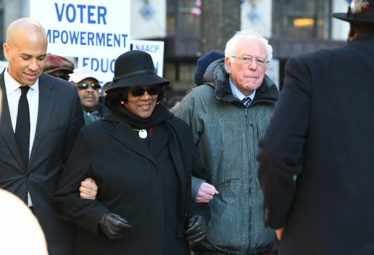 Following a Martin Luther King Jr. prayer service at Zion Baptist Church in Columbia, S.C., on Monday, Jan. 21, 2019, New Jersey Sen. Cory Booker, D-N.J., left, and Sen. Bernie Sanders, I-Vt., right walk with NAACP President Brenda Murphy during a march to the Statehouse. (AP Photo/Meg Kinnard)