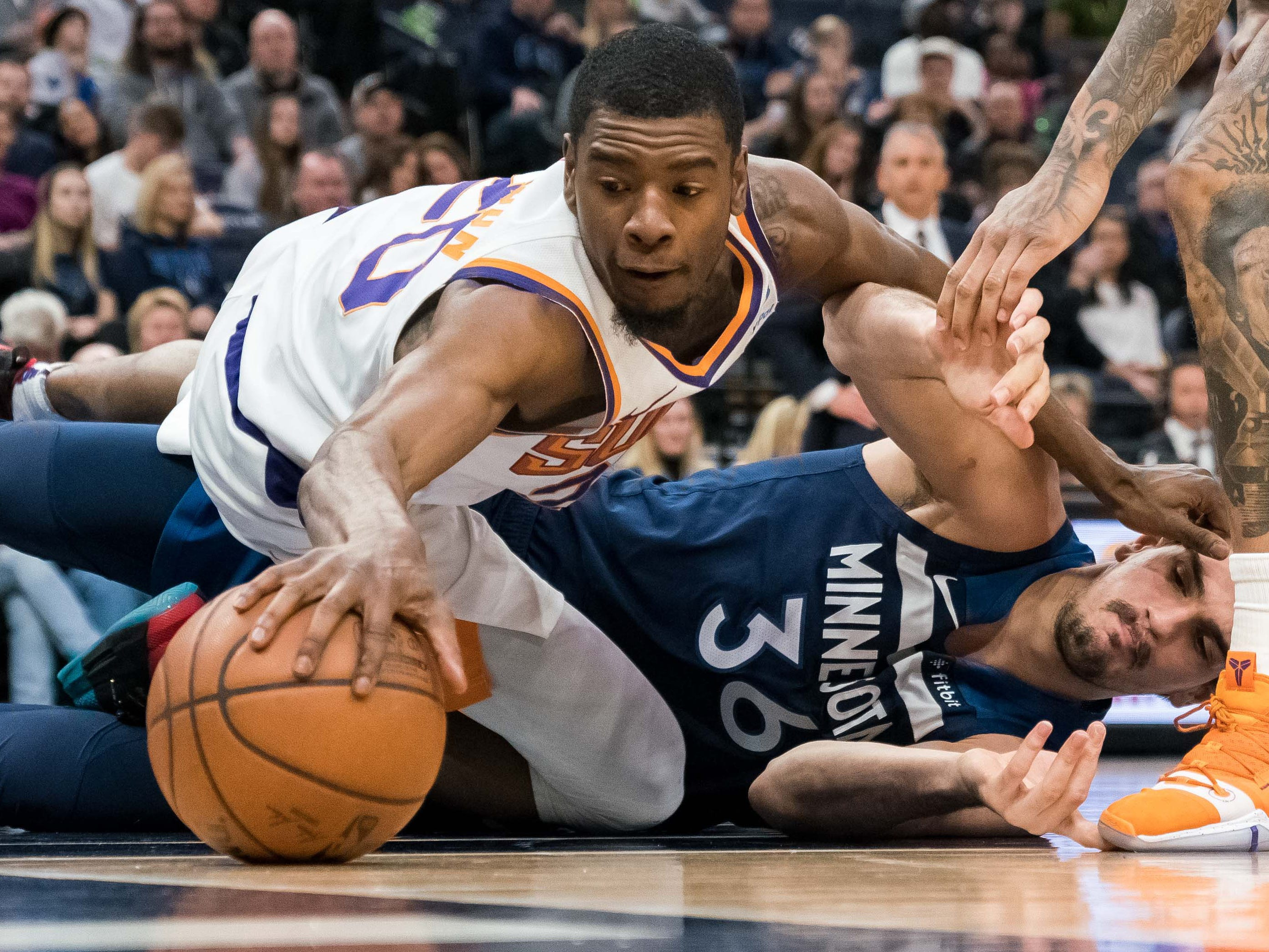 Jan. 20: Suns forward Josh Jackson (20) dives T'wolves forward Dario Saric (36) during a second-half scramble for a loose ball in Minneapolis.