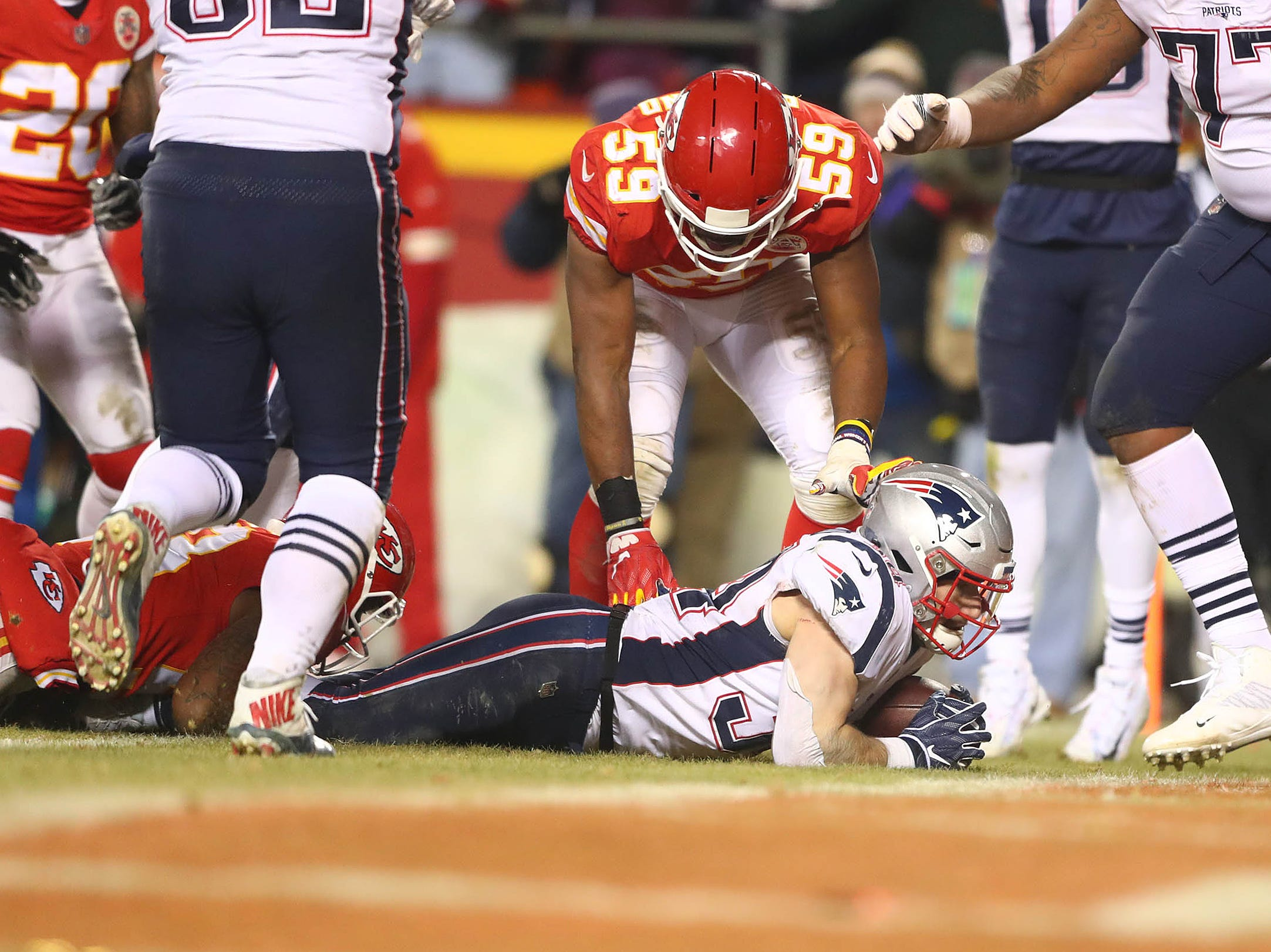 New England Patriots running back Rex Burkhead (34) scores a touchdown in front of Kansas City Chiefs inside linebacker Reggie Ragland (59) during the second half of the AFC Championship Game at Arrowhead Stadium.