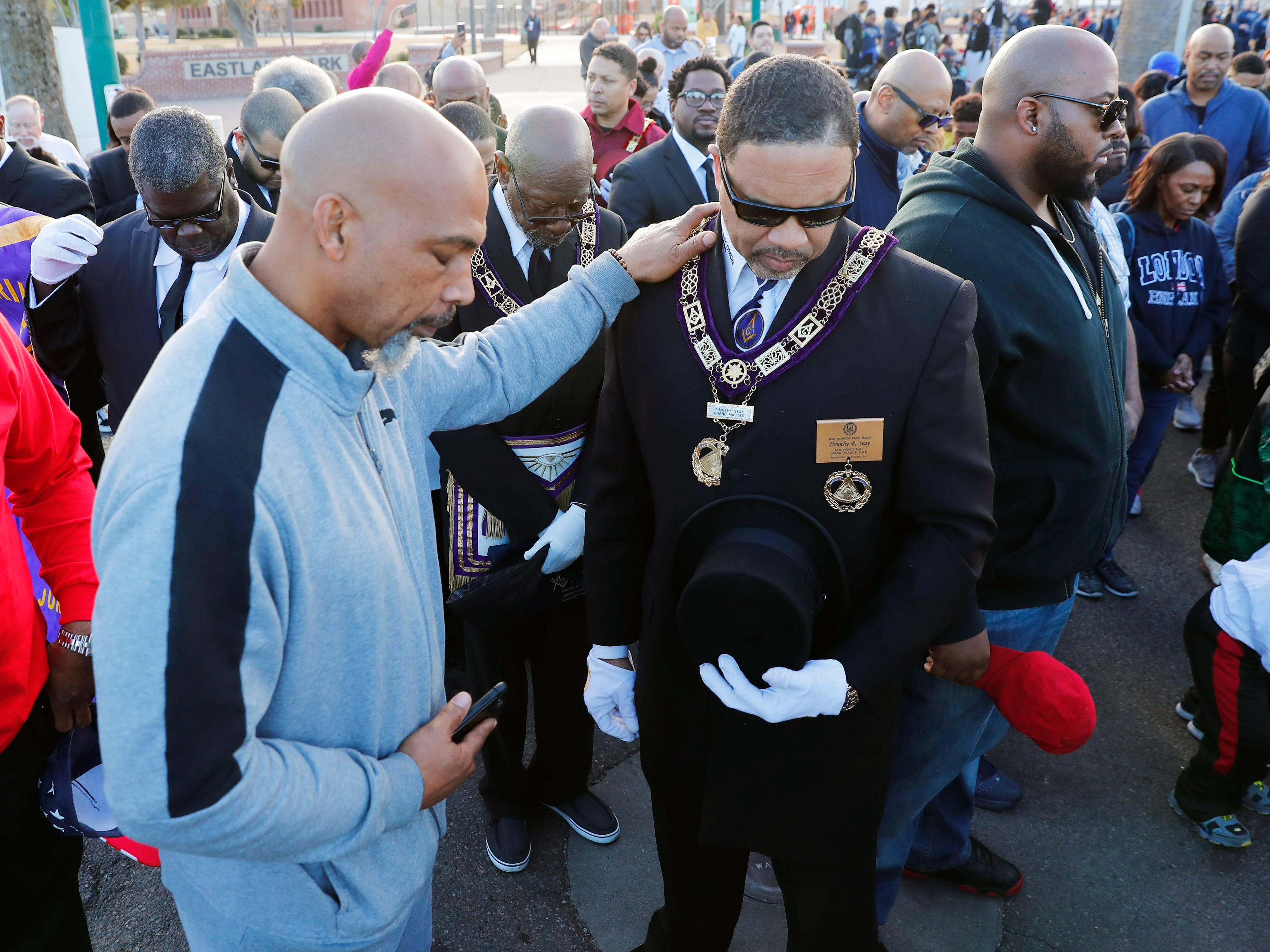 Kala Roy and Timmothy Seay bow their heads in prayer before marching honoring Dr. Martin Luther King in downtown Phoenix, AZ.
