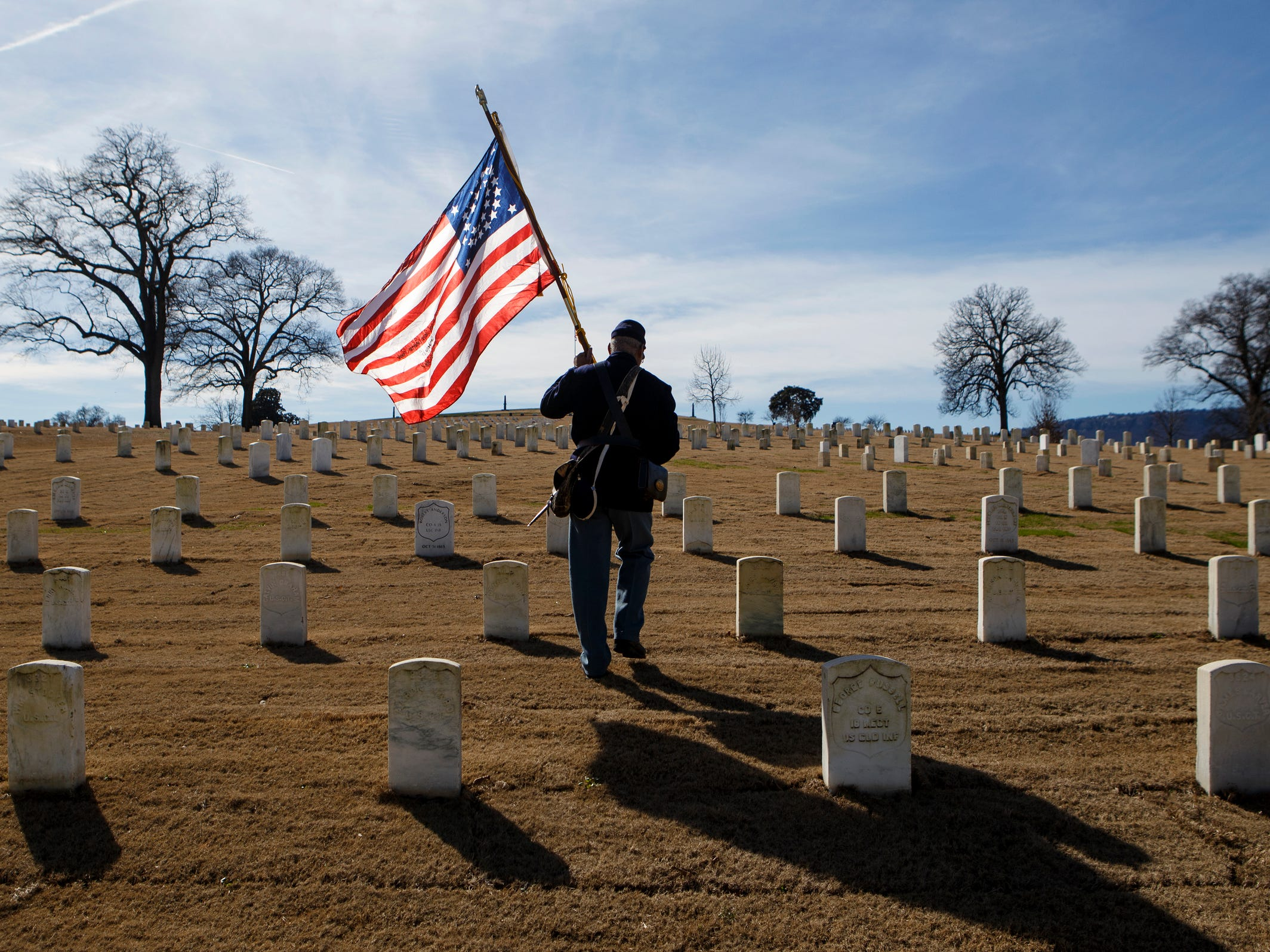 Donald Tatum, a quarter master sergeant in the 44th United States Colored Troops historical re-enactment group, carries a Civil War-era American flag through the Chattanooga National Cemetery before a wreath laying ceremony as part of the Martin Luther King Jr. Day of Service in Chattanooga, Tenn.
