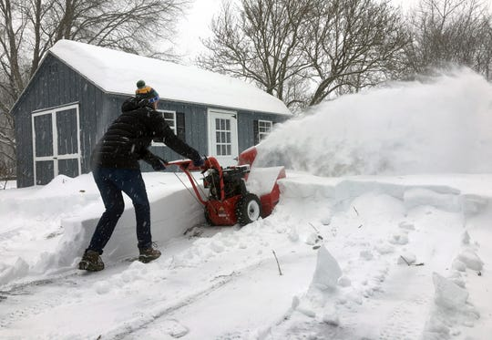 Ben Jennings snowblows his driveway on Jan. 20, in Glenville, N.Y., where 16 inches of snow fell.