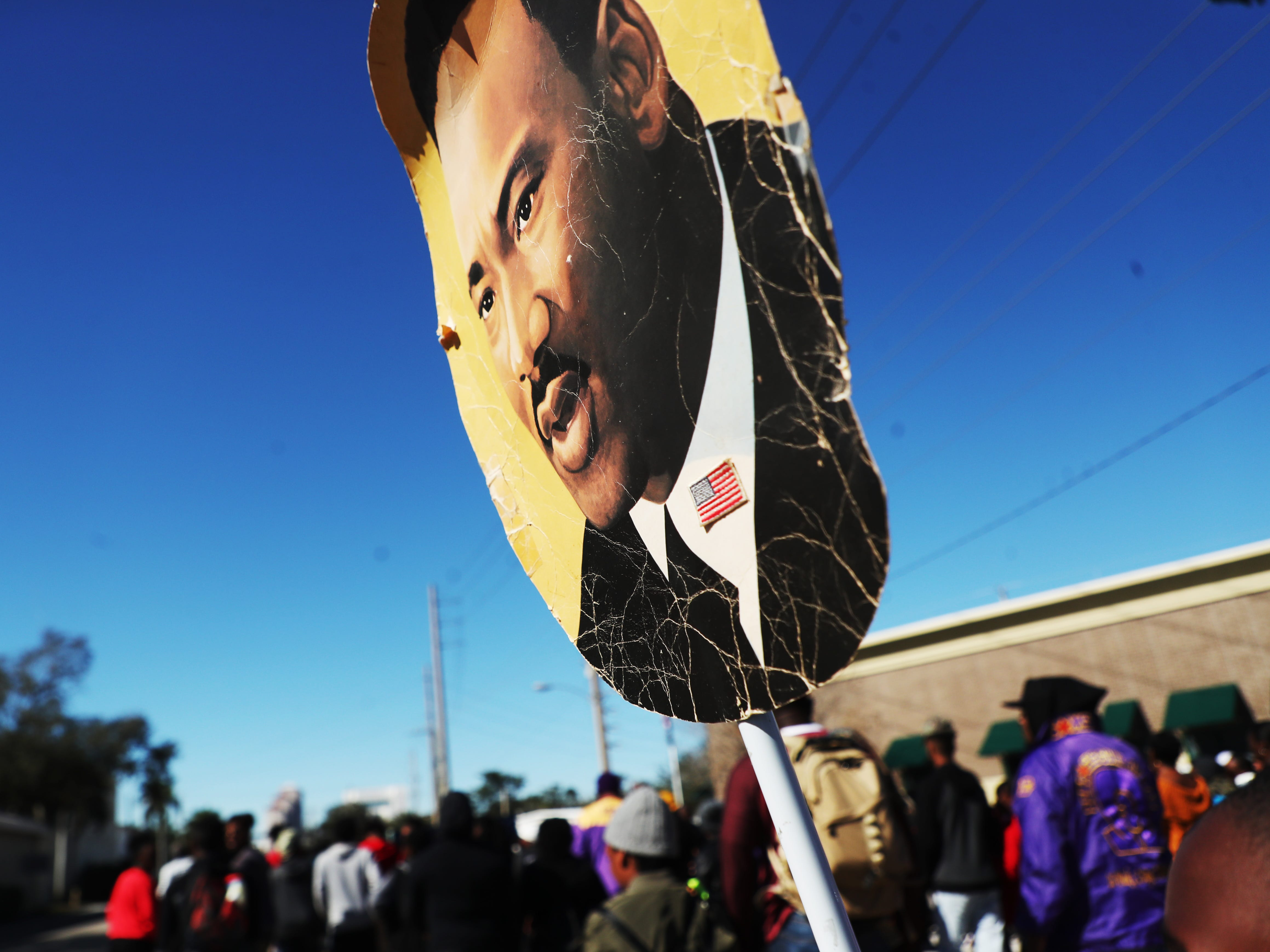 Roman Crump,8, marches with a more than 30 year old picture of Martin Luther King during the annual Martin Luther King Jr. Commemorative March  in Fort Myers Fla.