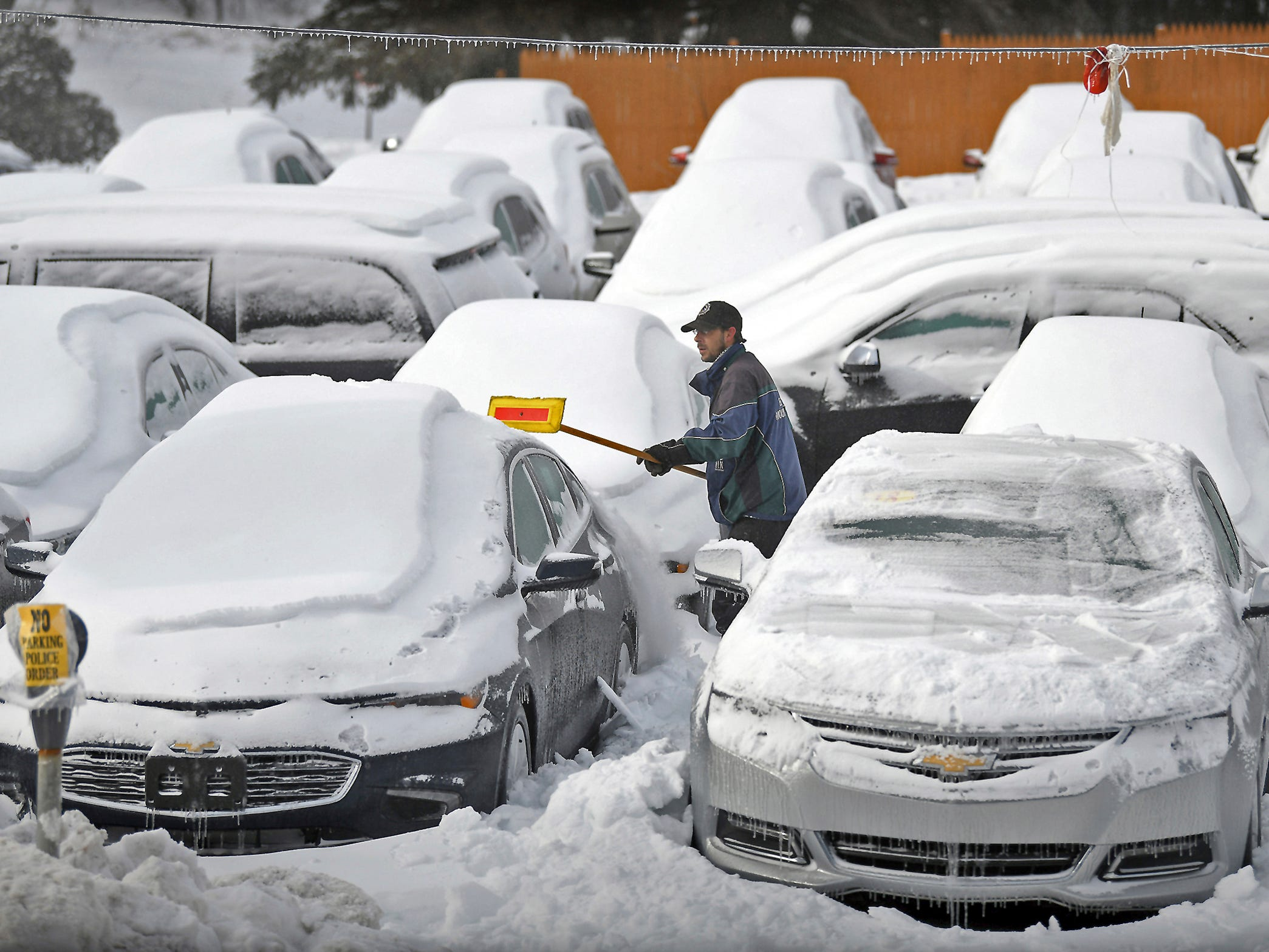 Leo Brunori an employee for Hornbeck Chevrolet, in Forest City, Pa., clears away ice and snow in a frozen parking lot of used vehicles.