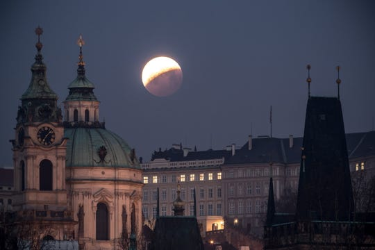 The super blood wolf moon is seen over the Church of Saint Nicholas in Prague, Czech Republic.