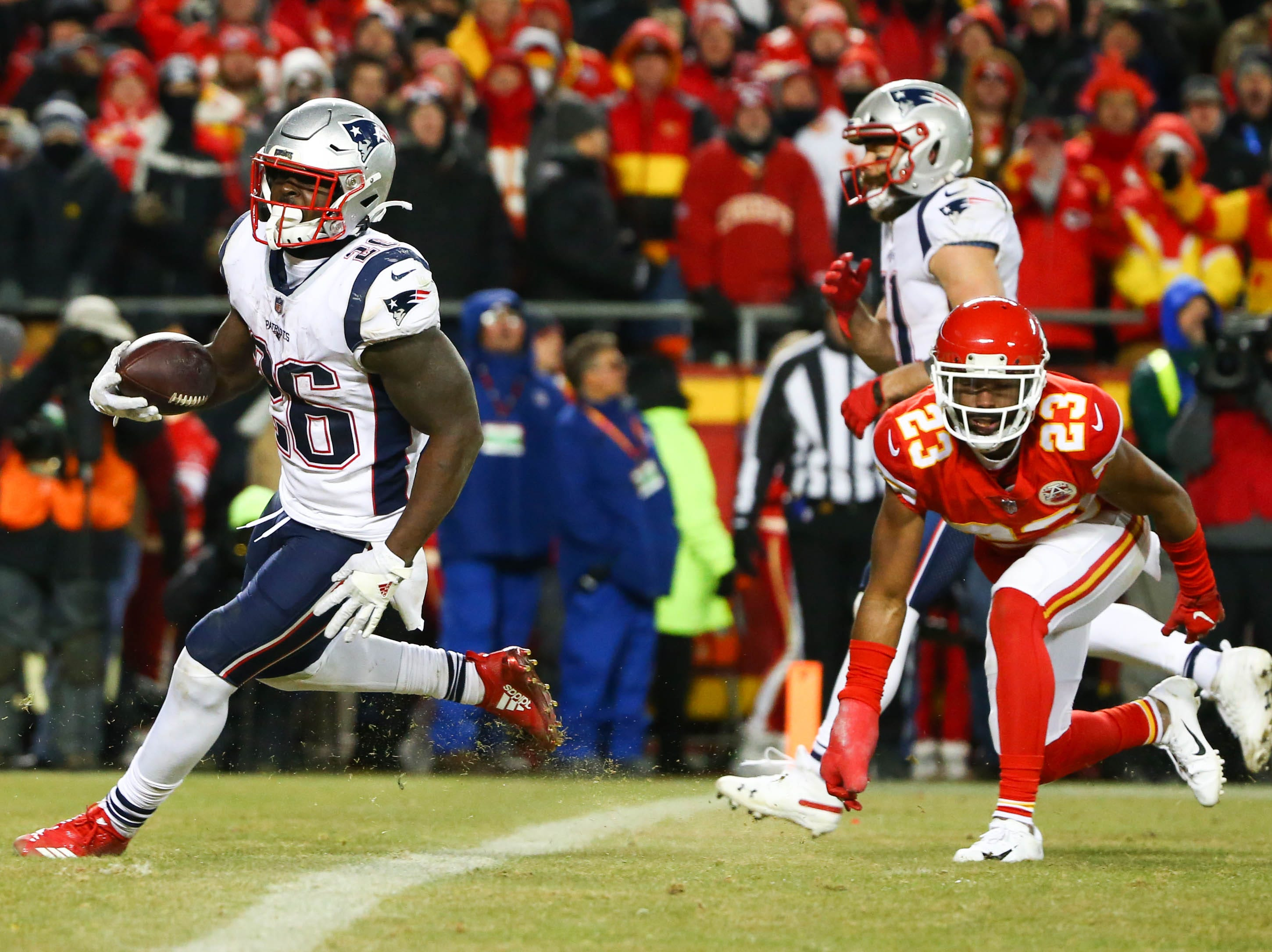 New England Patriots running back Sony Michel (26) runs the ball for a touchdown ahead of Kansas City Chiefs cornerback Kendall Fuller (23) during the second half of the AFC Championship Game at Arrowhead Stadium.