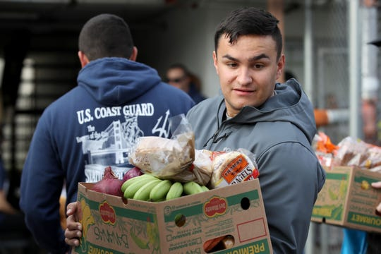 A U.S. Coast Guard member carries a box of free groceries during a food giveaway Jan. 19 in Novato, Calif. The Delaware Food Bank has set up a special program set up for furloughed federal workers.