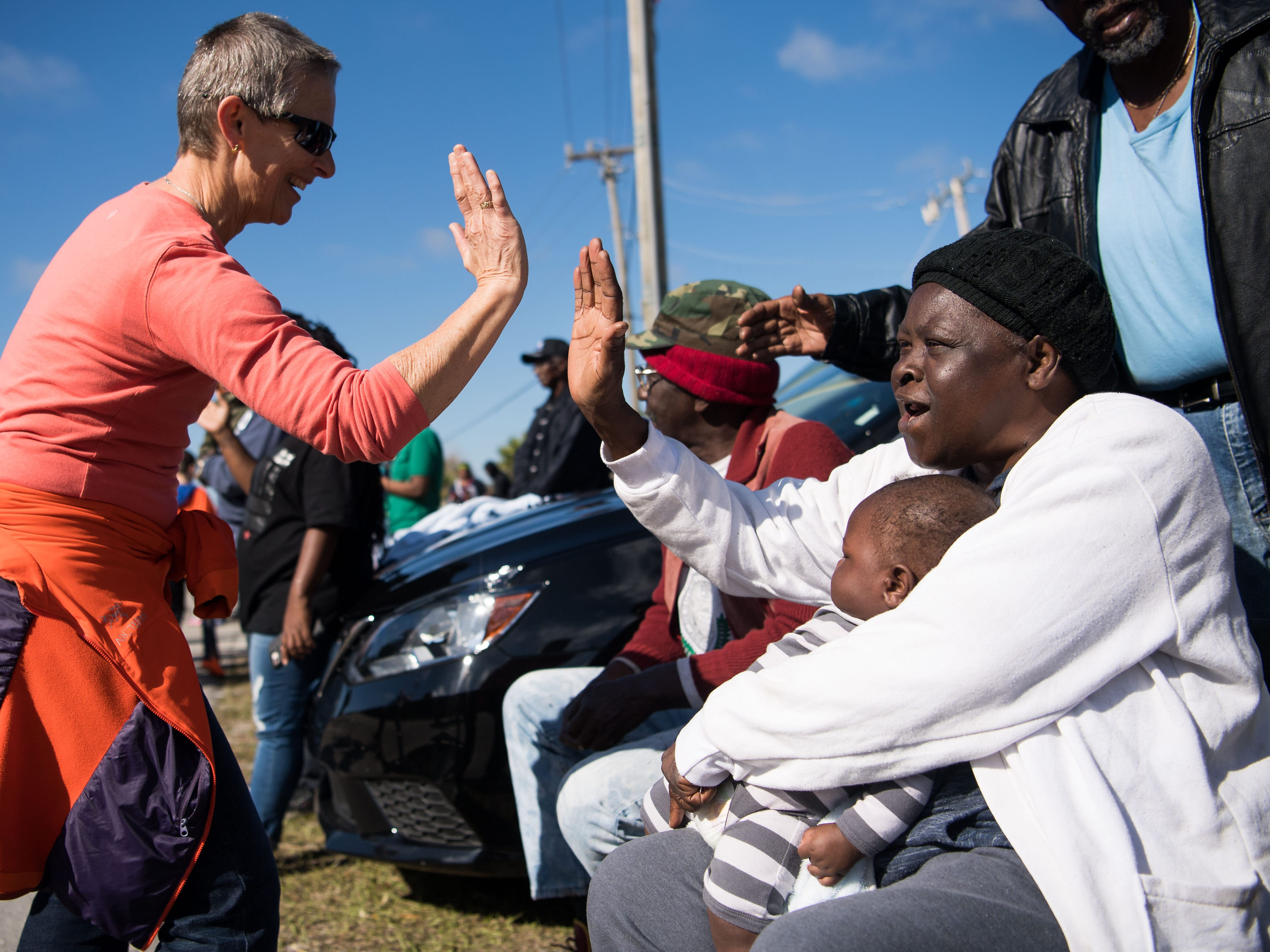 "Lifelong Gifford resident Corine Smith surrounded by her grandchildren and great-grandchildren and other family members is high-fived by Dhumavati Jaya during the 2019 MLK Parade in Gifford, Fla.  ""When they said he got shot, I was 10 years old at that time...I still listen to his speech, it means a lot,"" Smith said. ""God made us all, you know, he just made different colors,"" she added, ""but we are all his children."" The Dr. Martin Luther King Jr. Birthday Committee of Indian River County organized the parade, which ended in a festival at Gifford Park."
