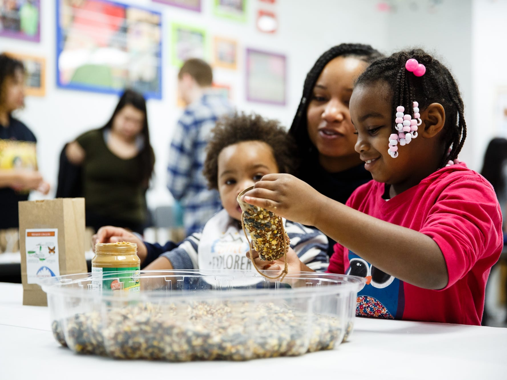 Elias Mitchell makes a bird feeder as her mother Jowelle watches during Martin Luther King Jr. day  activities at Community Youth Concepts in Des Moines, Iowa.