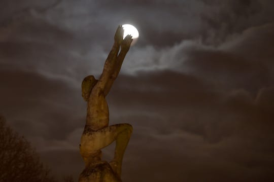 """The super blood wolf moon seen in Le Mans northwestern France behind the statue named """"L'envol""""."""