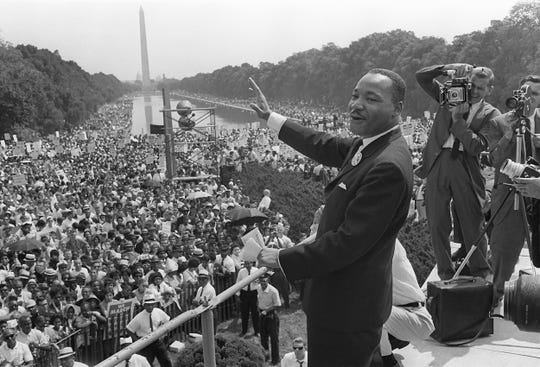 """In this file photo taken on August 28, 1963 The civil rights leader Martin Luther King waves to supporters during the """"March on Washington"""" on the Mall in Washington, DC."""