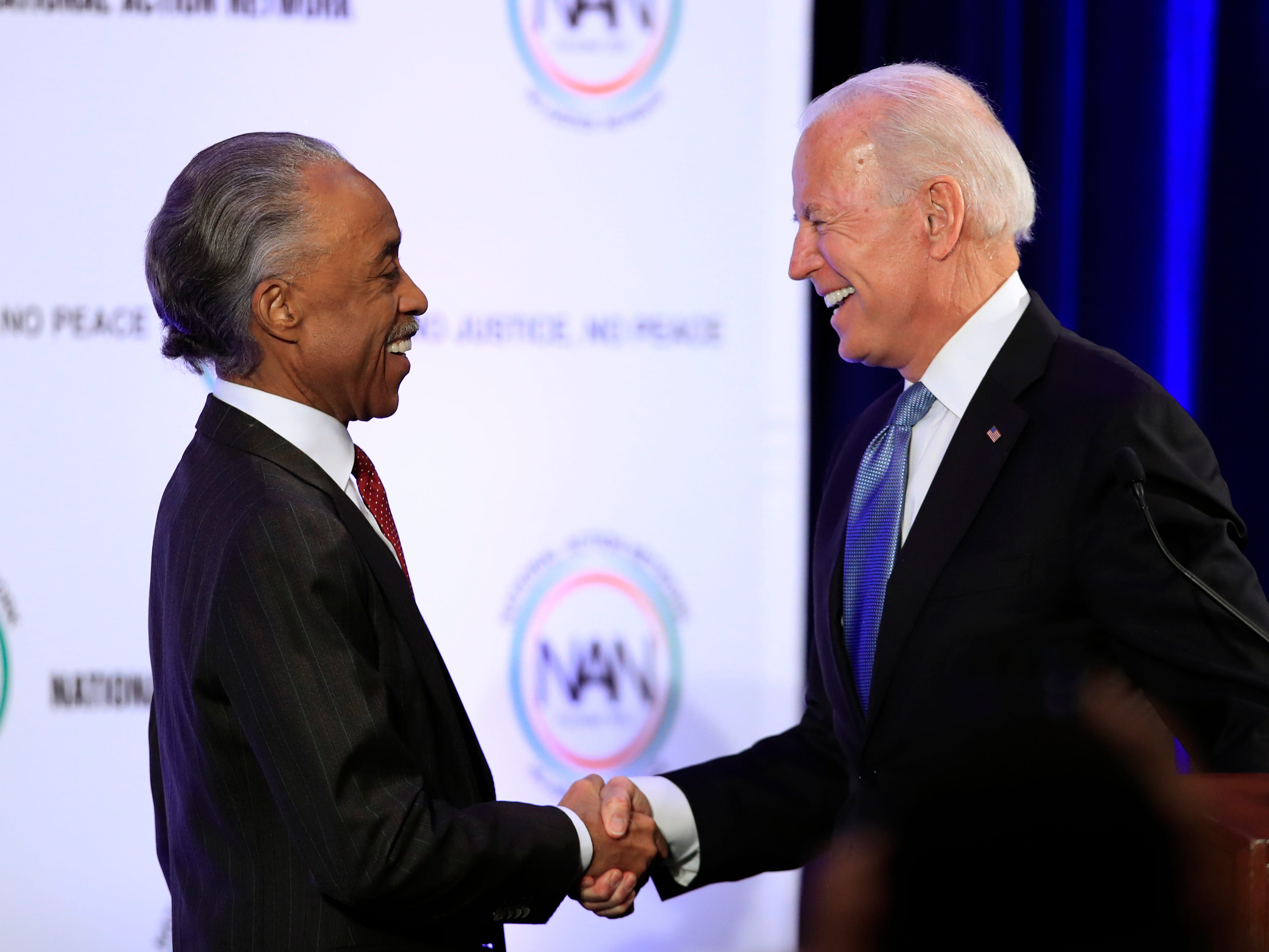 Former Vice President Joe Biden and Rev. Al Sharpton shake hands during a breakfast gathering commemorating the Martin Luther King Day in Washington.