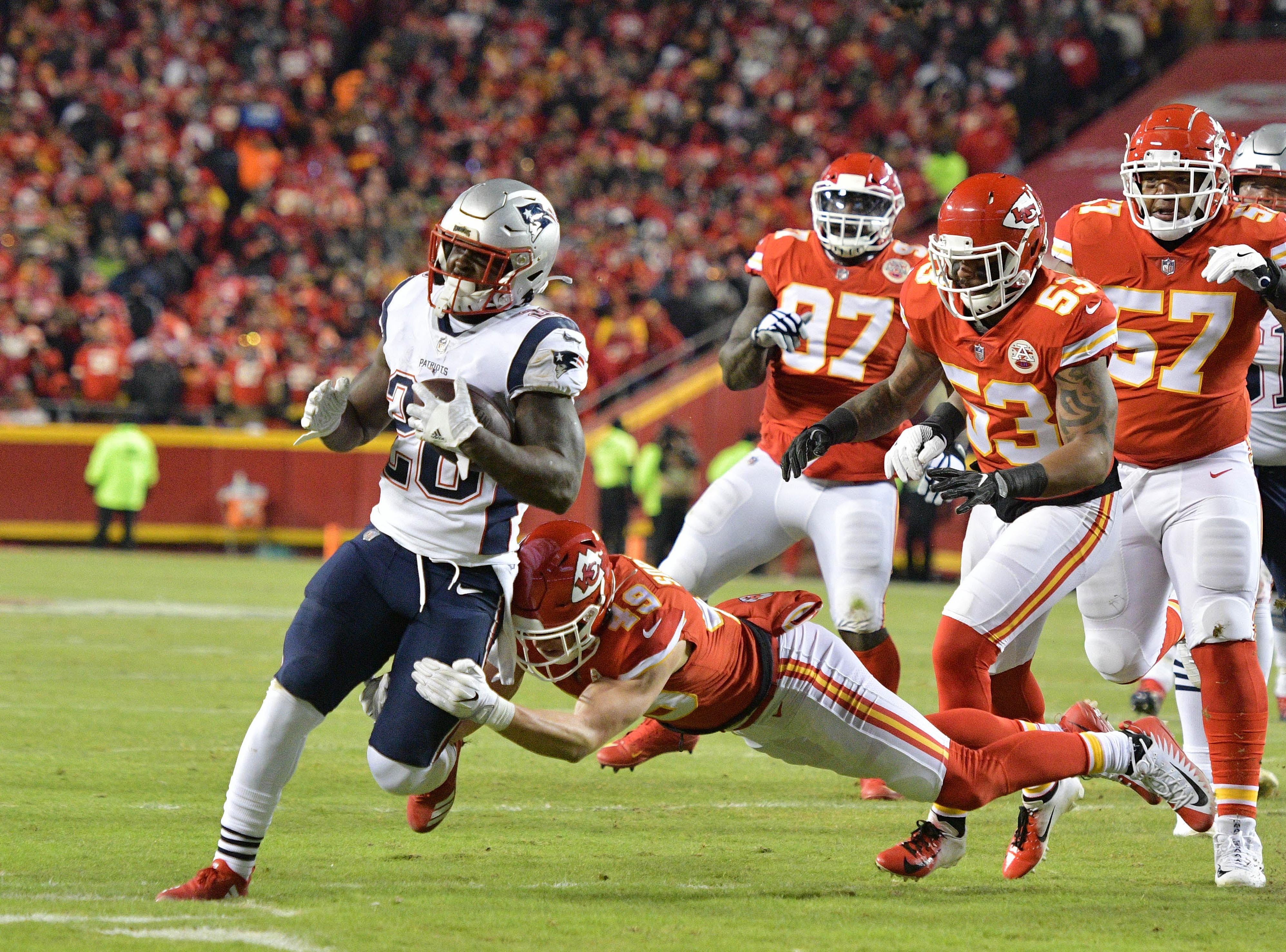 New England Patriots running back Sony Michel (26) carries the ball as Kansas City Chiefs defensive back Daniel Sorensen (49) defends during the first quarter.