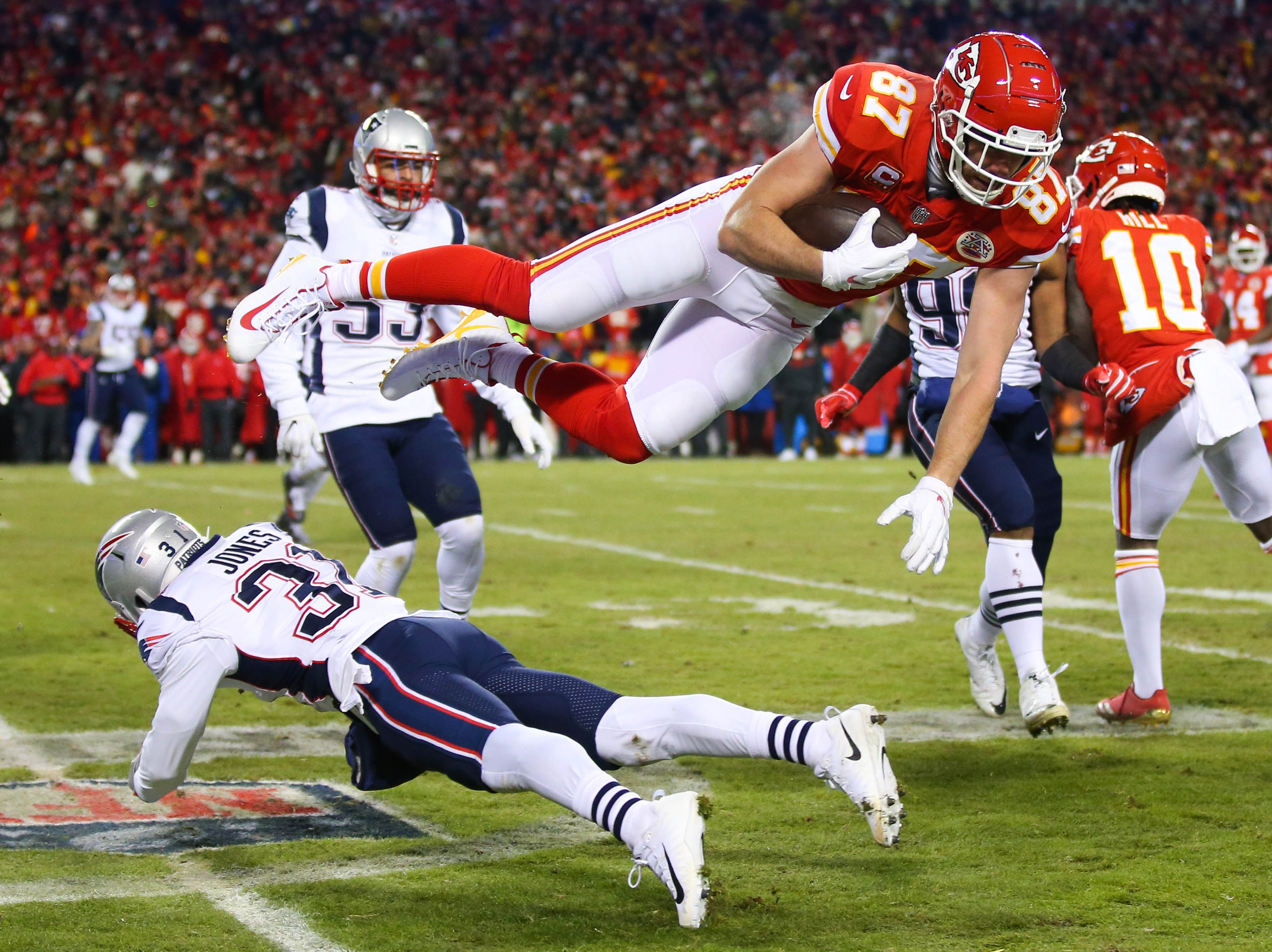 Kansas City Chiefs tight end Travis Kelce (87) leaps over New England Patriots defensive back Jonathan Jones (31) during the first half.