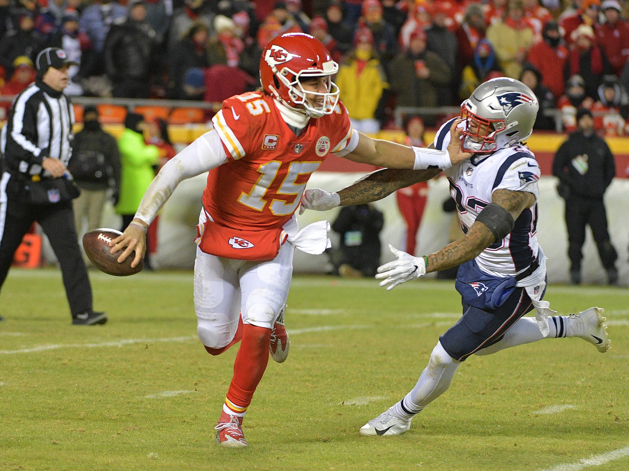 Kansas City Chiefs quarterback Patrick Mahomes (15) runs with the ball as New England Patriots strong safety Patrick Chung (23) defends during the second half of the AFC Championship Game at Arrowhead Stadium.