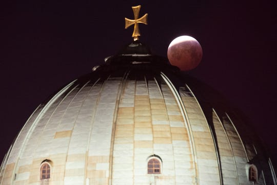 A view of the lunar eclipse over the cross on top of the Elizabeth Church in Nuremberg, Germany. The entire eclipse was visible from North and South America, as well as parts of western Europe and north Africa.