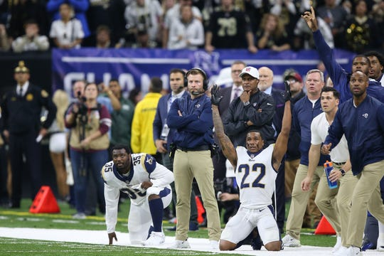 Los Angeles Rams head coach Sean McVay (standing) and running back C.J. Anderson (35) and cornerback Marcus Peters (22) watch a field goal attempt against the New Orleans Saints during overtime of the NFC Championship game at Mercedes-Benz Superdome.