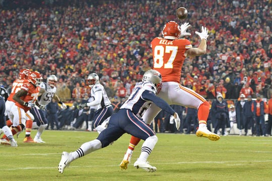 Kansas City Chiefs tight end Travis Kelce (87) catches a touchdown pass in front of New England Patriots defensive back J.C. Jackson (27) during the second half of the AFC Championship Game at Arrowhead Stadium.