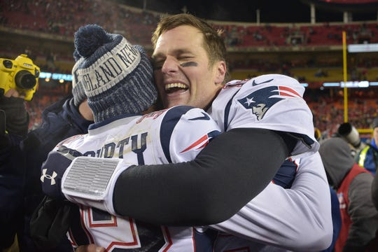 New England Patriots quarterback Tom Brady (12) celebrates with Patriots free safety Devin McCourty (32) after defeating the Kansas City Chiefs during overtime in the AFC Championship Game at Arrowhead Stadium.