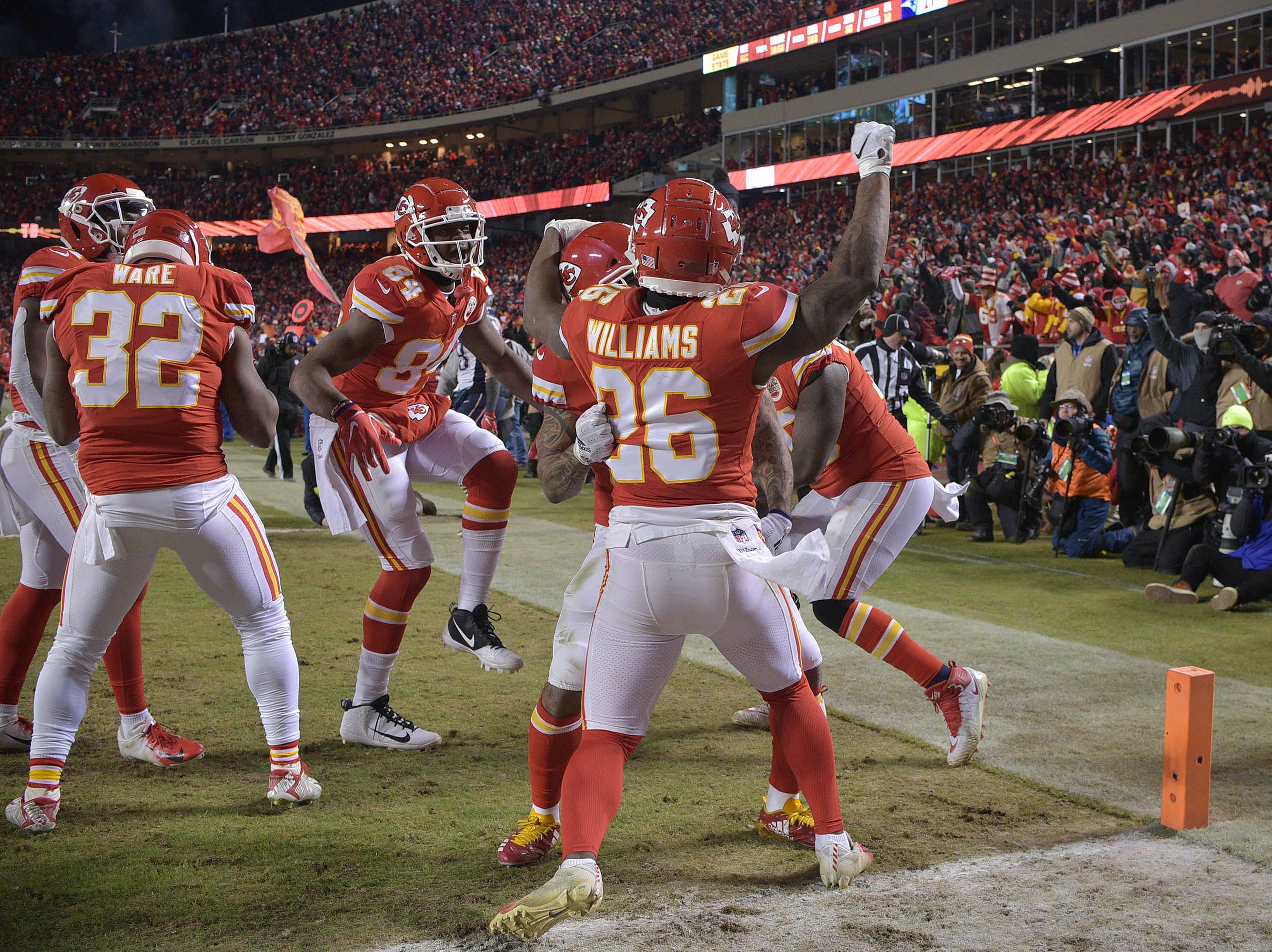 Kansas City Chiefs running back Damien Williams (26) celebrates with teammates after a touchdown against the New England Patriots during the second half of the AFC Championship Game at Arrowhead Stadium.