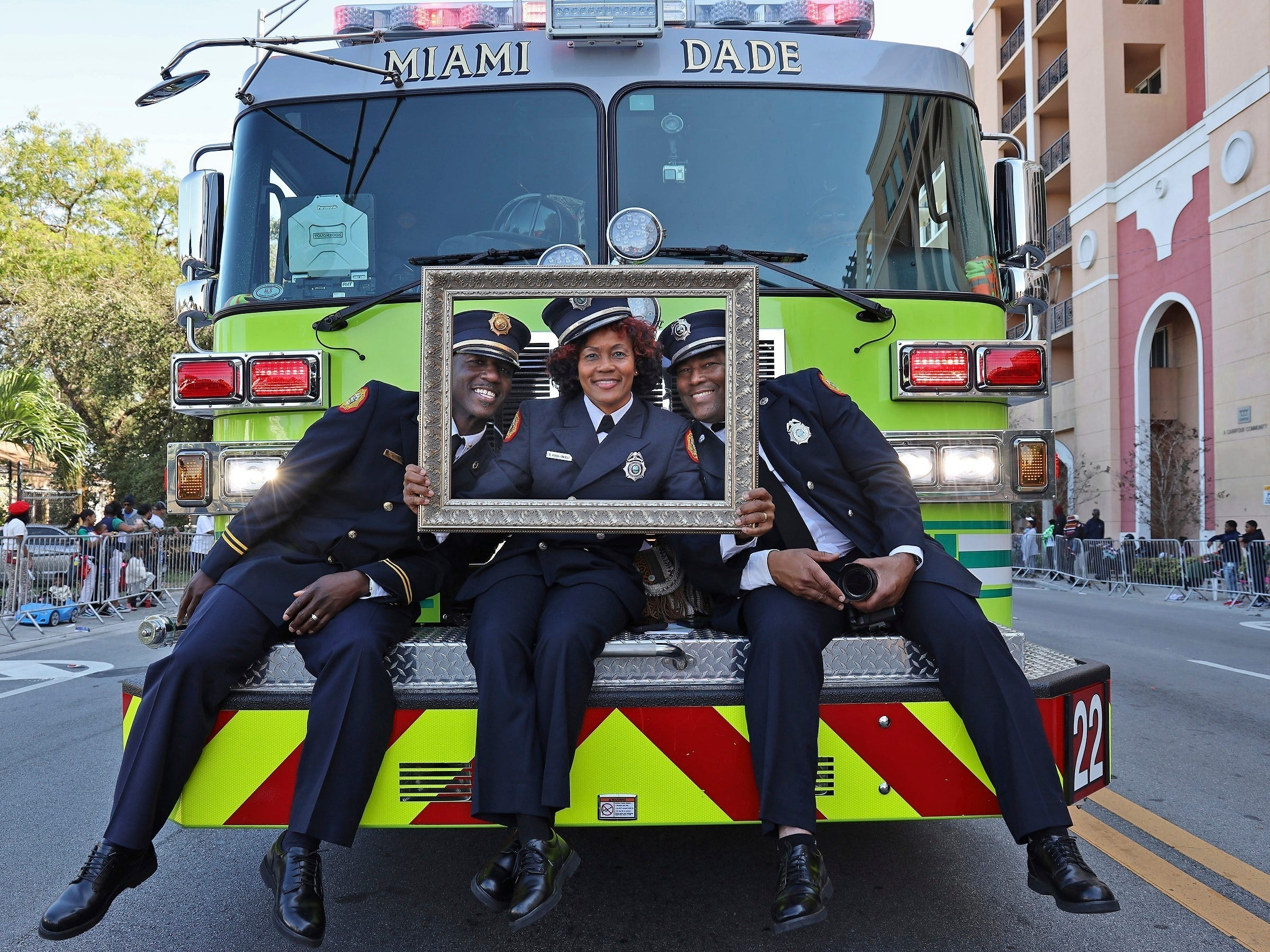 Ranking Black Miami-Dade Fire and Rescue personal ride on the front bumper of fire truck during the MLK Day Parade in Liberty City in Miami.