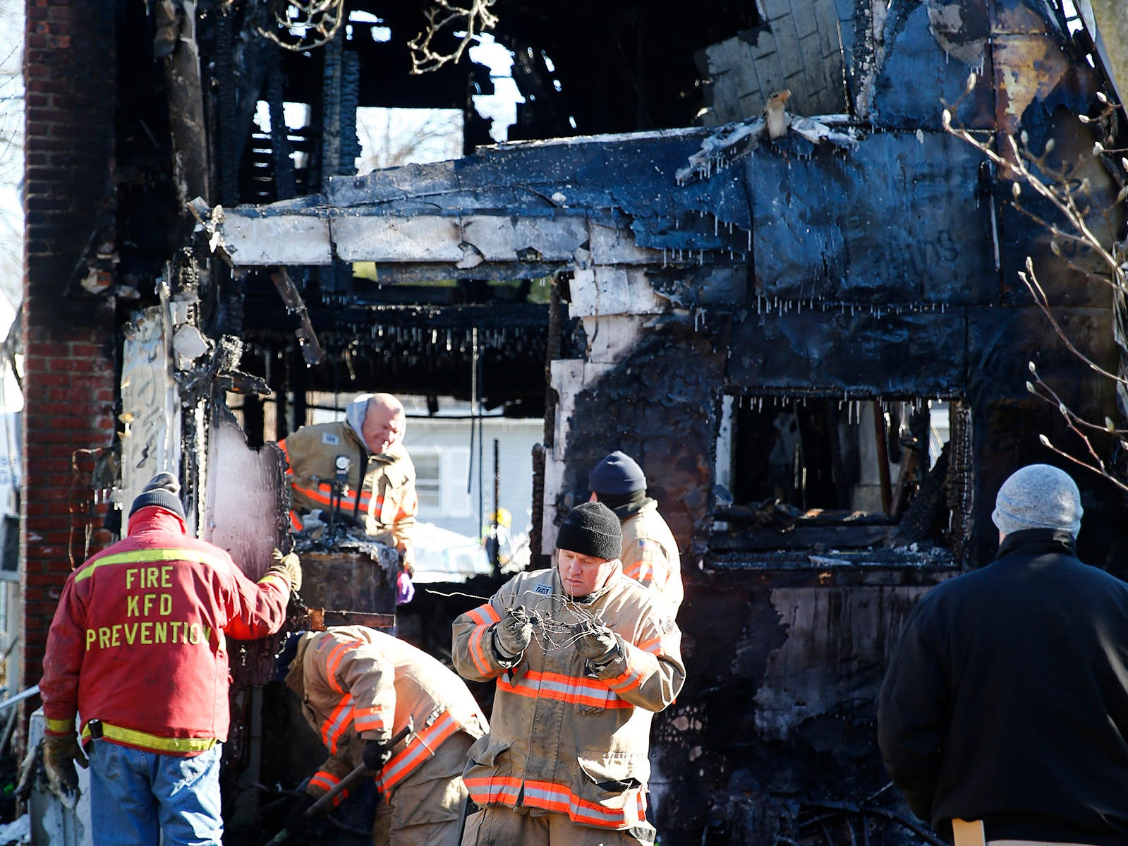 Investigators are shown behind a Cottage Place home in Keansburg Tuesday morning, January 22, 2019, that was gutted by a fire.