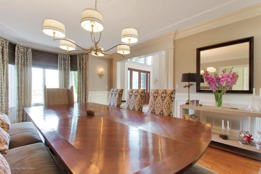 The formal dining room features hardwood flooring, custom windows, and decorative crown molding.