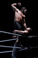Seth Rollins moves to deliver a downward strike on Dean Ambrose during Saturday's WWE Live wrestling event.