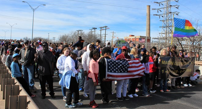 MLK bridge marchers pause Monday and their return. Another large crowd turned out and braved whipping wind for the afternoon event.